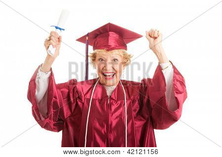 Senior woman dressed in her graduation cap and gown, raises her arms in excitement over getting her college degree.  Isolated on white.