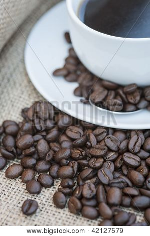 Close Up Of Coffe Cup And Saucer Surrounded By Beans On Hessian Background