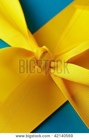 Knoten im gelben Geschenkband um ein blaues Paket
