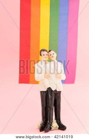 Gay groom cake toppers in front of rainbow flag on pink background