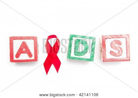 Wood blocks spelling aids using red ribbon on white background