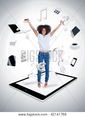 Cheerful woman jumping on a tablet pc against a digital gray background