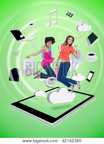 Two happy women jumping on a tablet pc against a digital green background