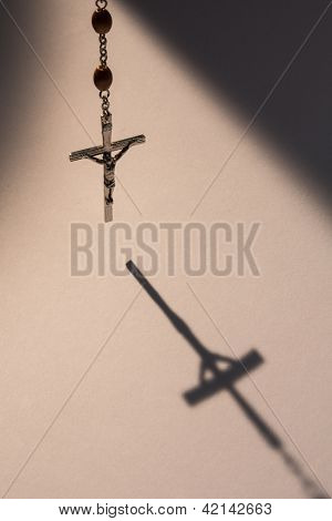 Crucifix from rosary beads hanging and casting a shadow
