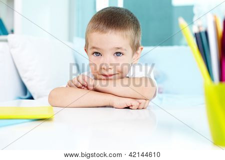 Adorable lad looking at camera while sitting by table