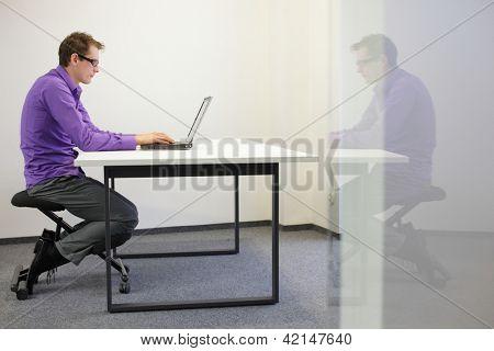 postura sentada ruim na estação de trabalho. homem na cadeira de joelhos