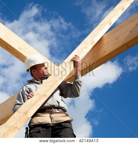 construction worker at work with timber  roof construction