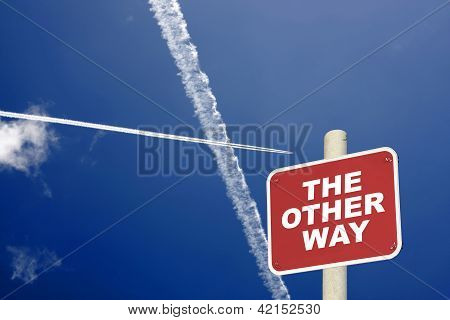 The Other Way Sign With Jet Trails Crossing A Blue Sky