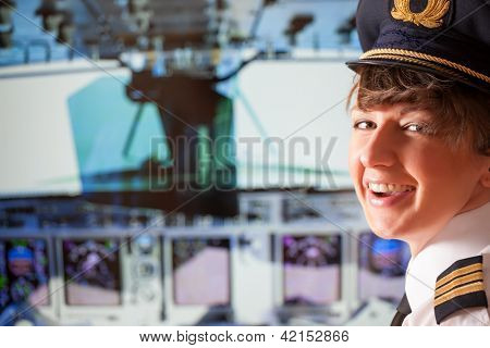Beautiful woman pilot wearing uniform with epaulets, hat with golden wings sitting inside airliner with visible cockpit during flight.