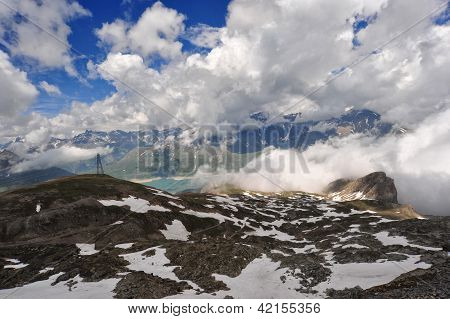 Summer In Mountain With Snow Clouds In The Sky