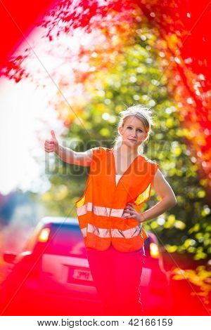 Young female driver wearing a high visibility vest on the roadside after her car has broken down