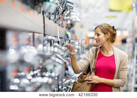 Pretty young woman choosing a bathroom/kitchen tap in a home furnishings retail store
