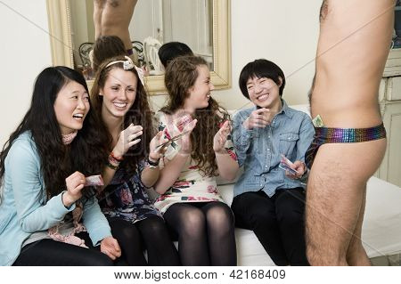 Cheerful young women enjoying while male stripper performing