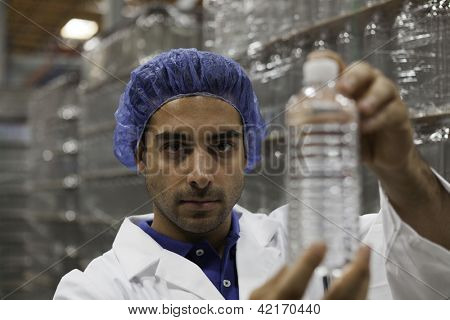 Portrait of factory worker holding water bottle