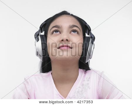Asian Teenage Girl Of Indian Origin Listening To Music