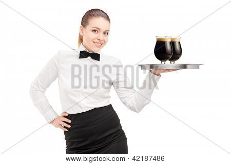 A waitress with bow tie holding a tray with two glasses of dark beer on it isolated on white background