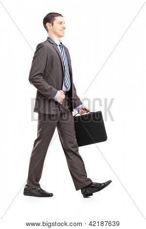 Full length portrait of a young businessman with briefcase walking isolated on white background