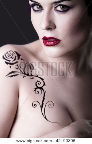 Sensual beautiful nude brunette girl with tribal tattoo rose