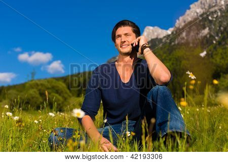 Young man with mobile phone sitting in the meadow with mountain views calling