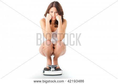 Diet and weight, young woman sitting on her haunches on a scale