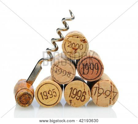Closeup of a group of vintage dated wine corks and an antique corkscrew on white with reflection.