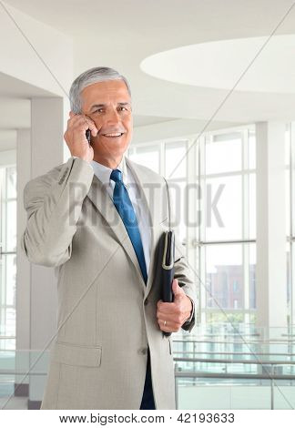 Portrait of a middle aged businessman standing in a modern office talking on a cell phone.. Man is holding a small binder and smiling at the camera.