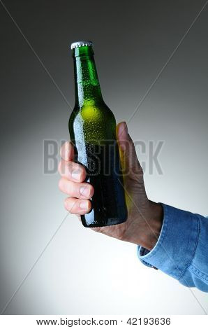 Closeup of a man's hand holding a green beer bottle over a light to dark gray background. Vertical format. Bottle has no label and is covered with condensation.