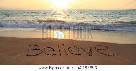 Believe written in the sand at the beach