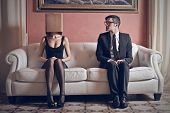 foto of shy woman  - man looks at beautiful woman with box on his head sitting on the couch - JPG