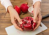 Hands opening a pomegranate and showing the seeds