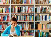 stock photo of clever  - Portrait of clever student with open book reading it in college library - JPG