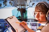 Beautiful woman pilot wearing uniform with epauletes and headset, writting on notepad inside airline