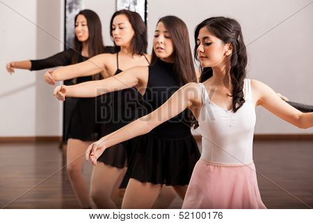 Beautiful dancers training on barre