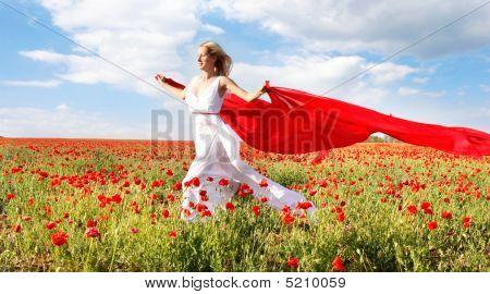 Feliz mujer con pañuelo rojo en el campo de amapolas