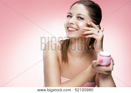 Applying cosmetic cream on face