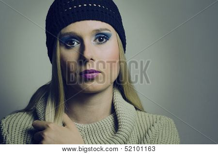 fashion portrait of a blond woman wearing a turtleneck and a hat