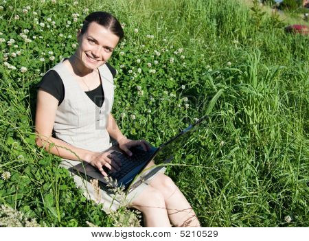Girl With A Laptop Relaxing In The Grass
