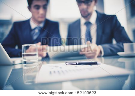 Image of business objects on background of two young businessmen discussing document in touchpad at meeting