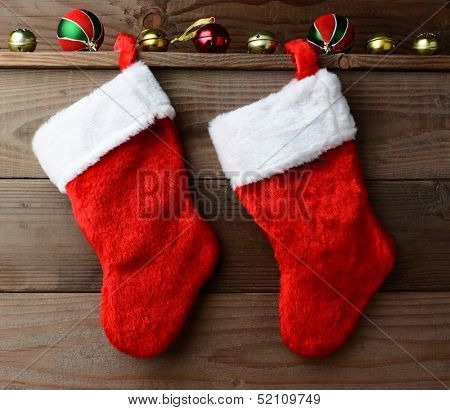 Christmas stockings hung on a rustic wooden wall with sleigh bells and ornaments.