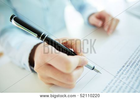 Close-up image of a business woman going to put her signature