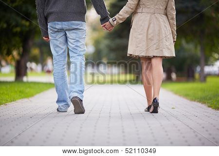 Legs of couple walking in park