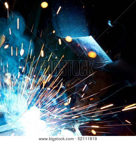 Welders in action with bright sparks. Construction and manufacturing theme.