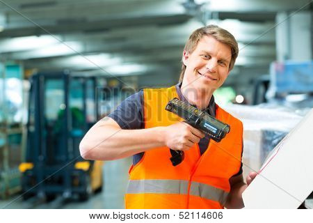 Logistics - Warehouseman with protective vest and scanner, scans bar-code of package, he standing at warehouse of freight forwarding company