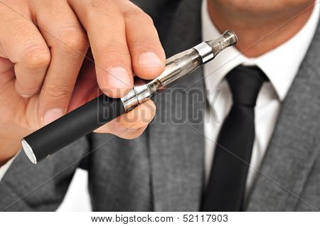 man wearing a suit vaping with an electronic cigarette