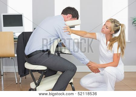 Masseuse treating clients arm in massage chair in bright room