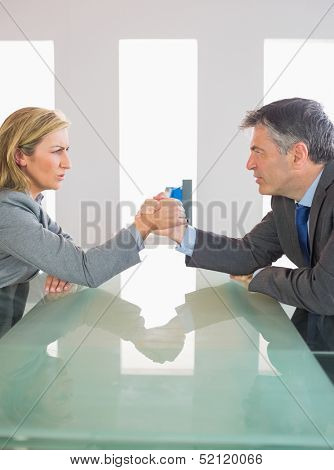 Two annoyed mature businesspeople having an arm wrestling sitting around a table at office