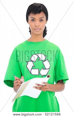 Unsmiling black haired ecologist writing on a notebook on white background