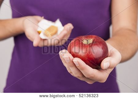 Young woman preffering candy instead of fruit