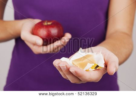 Young woman preferring fruit instead of candy