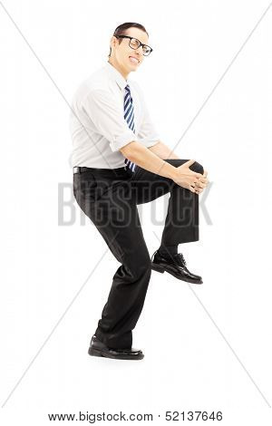 Full length portrait of a young man holding his knee because of pain isolated on white background